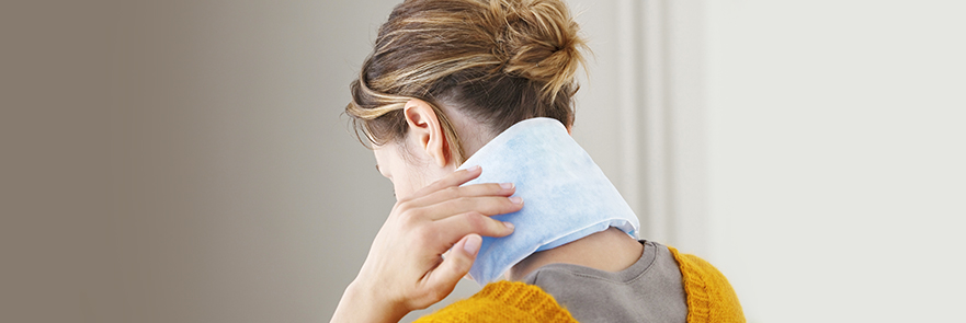 Woman holding heat pad to her neck.