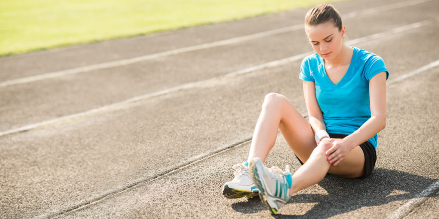 Woman sitting on running track holding knee