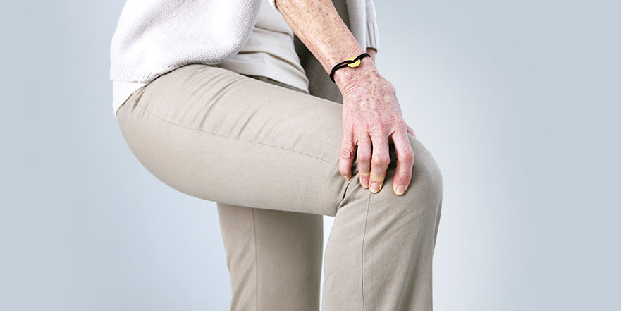 Woman with Osteoarthritis holds knee.