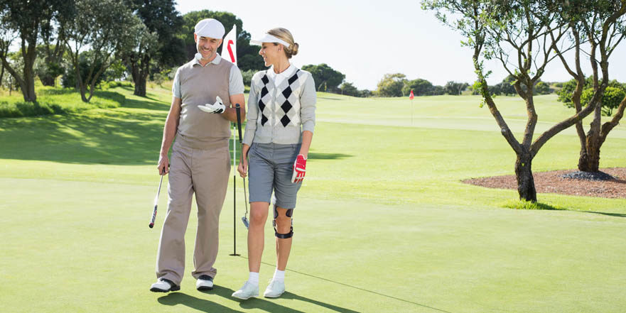 A man and a woman dressed in golf attire. The woman is wearing an OdrA Knee brace.