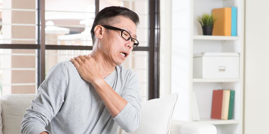 Asian man with rotator cuff related shoulder pain, pressing on neck and shoulders with painful expression