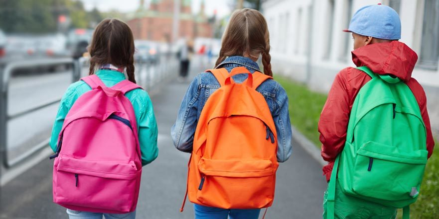 Three Children with neon coloured backpacks walk down a busy city street.