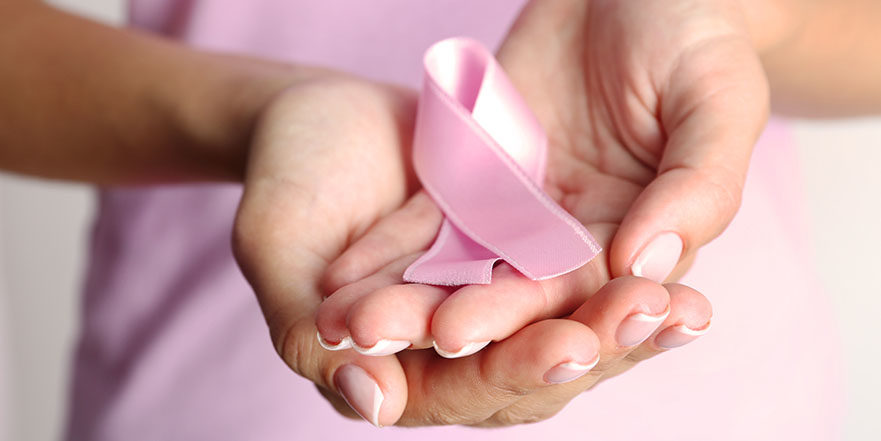 Hands hold a pink breast cancer awareness ribbon.