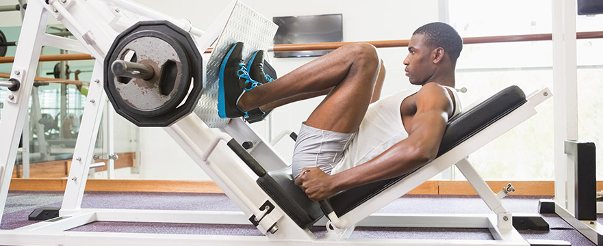 photo of a man using a leg press in a gym