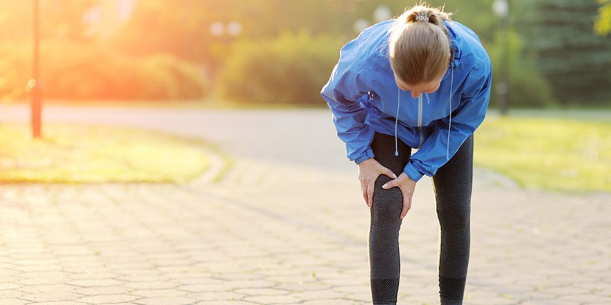 Woman in athletic gear out for jog holding knee in pain