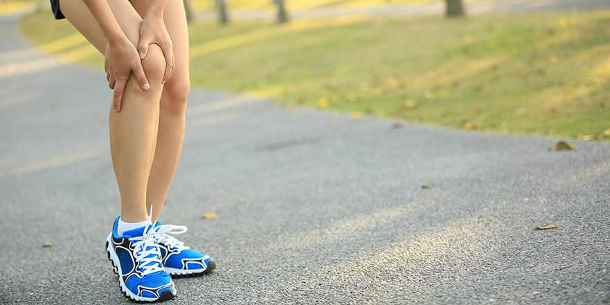 Photograph of a woman runner holding their knee due to ACL injury
