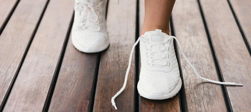 Photograph of a woman loosening the laces on her sneakers