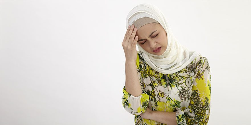 Photograph of a woman holding her head due to migraine pain