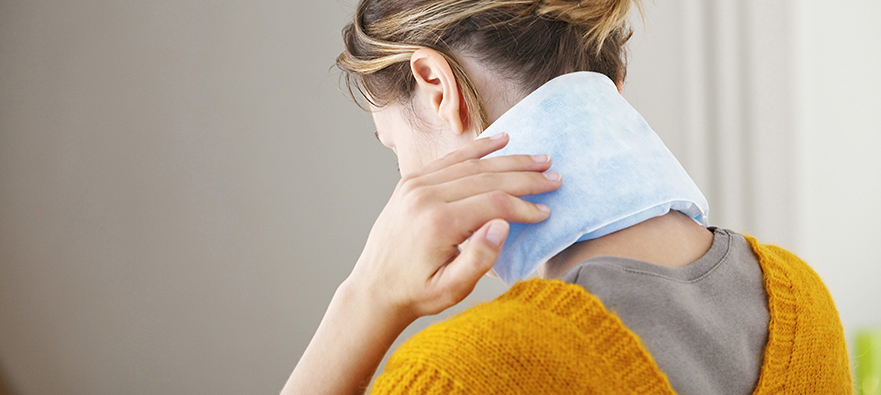 Photo of a womn using cold therapy for migraine headache relief. She is placing a cold pack over the carotid arteries in her neck.