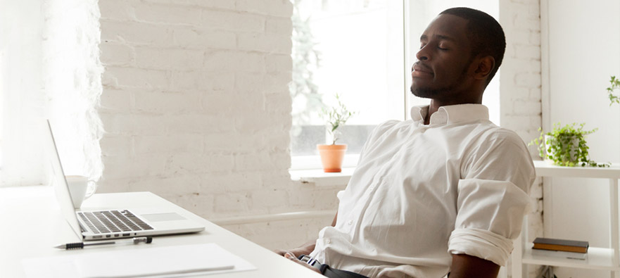 Photograph of a man sitting at a work desk, taking a break to breathe deeply