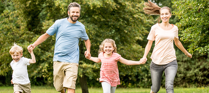 photograph of a family running through the park holding hands