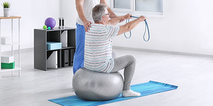 photograph of a man on an exercise ball as part of post-heart surgery cardiac rehabilitation physiotherapy