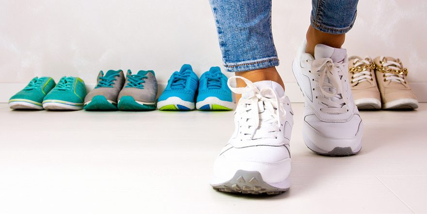 photograph of a woman trying on different sneakers designed for overpronation