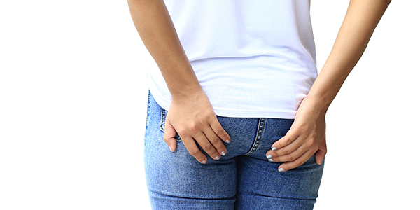 Photograph of woman holding her buttocks where it's affected by bursitis.