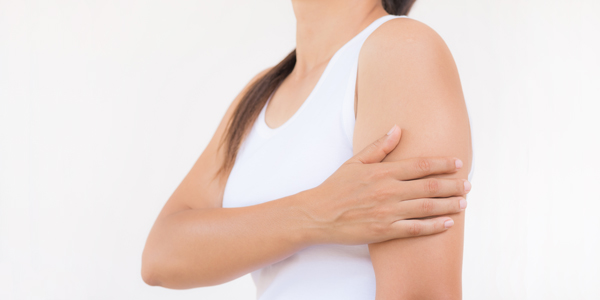 photograph of a woman holding her biceps due to biceps tendonitis