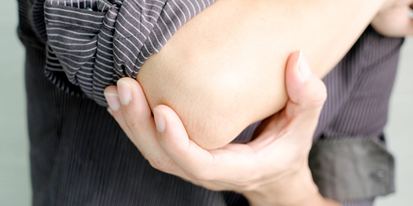 Photograph of man holding his bursitis elbow.