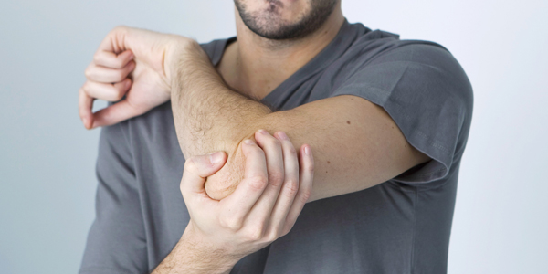 photograph of a man holding his elbow due to tennis elbow pain