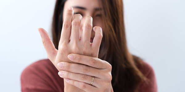 photograph of a woman holding her sprained fingers