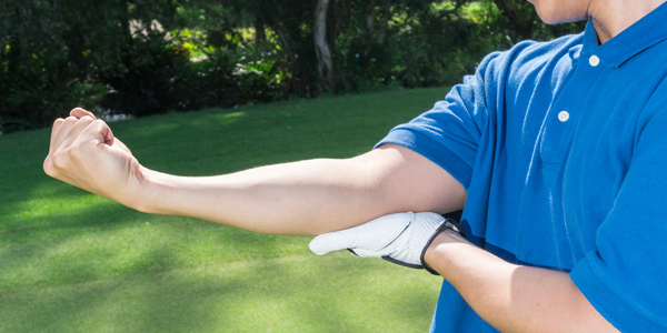 photograph of a male golfer holding hte inside of his elbow due to golfer's elbow pain