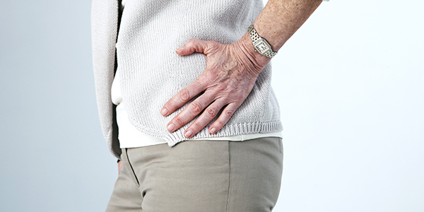 Photograph of woman holding hip effected by bursitis.