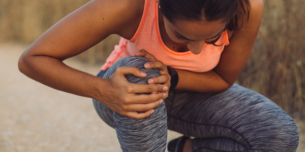 photograph of a woman holding her knee due to jumper's knee pain
