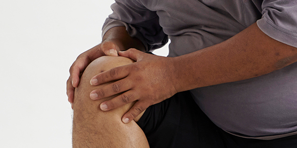 Photograph of man holding knee effected by bursitis.