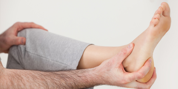 photograph of a man holding his foot due to Peroneal tendinosis