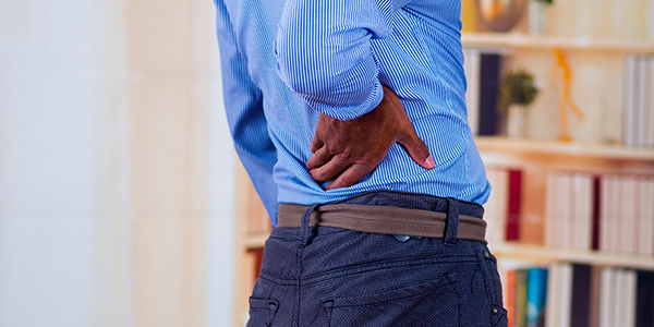 Image of middle aged man holding his lower back.