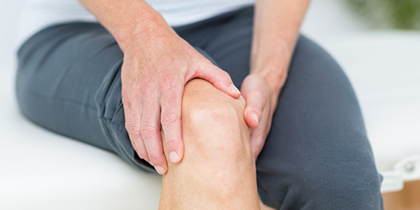 Image of woman holding her knee because of a meniscal tear.