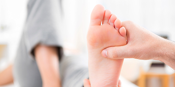 Image of woman being treated by a physiotherapist for her plantar fasciitis.