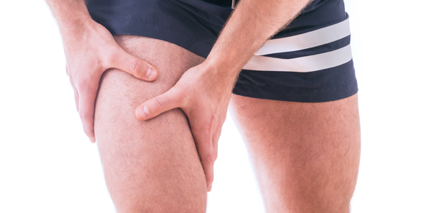 photograph of a man holding his quads due to painful tendonitis