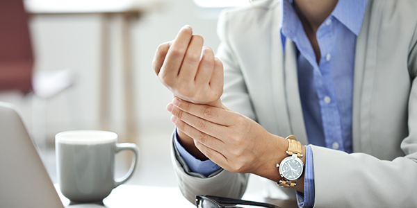 Image of woman holding her wrist because of a repetitive strain injury, carpal tunnel.