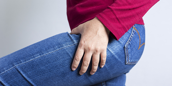 Photograph of woman holding her thigh effected by bursitis.