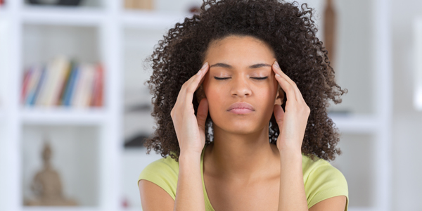 photograph of a woman holding her head due to an anxiety induced headache