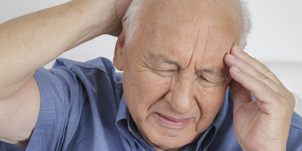 photograph of an elderly man holding his head due to a brain tumour induced headache