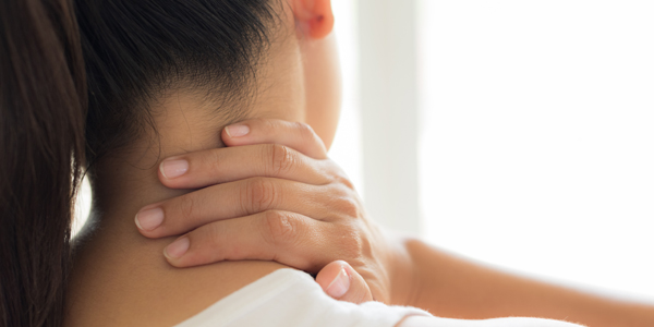 photograph of a woman with degenerative disc disease of the neck holds her neck in pain
