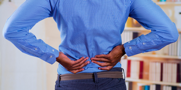 photograph of man holding his low back due to pain from degenerative disc disease