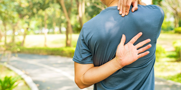 photograph of a man holding his upper back due to degenerative disc disease pain