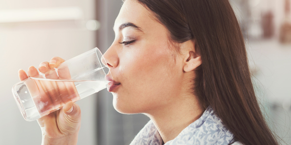 photograph of a woman drinking water to help ease a dehydration headache