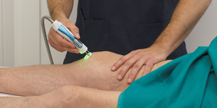 photograph of a physiotherapist performing laser therapy for pain relief