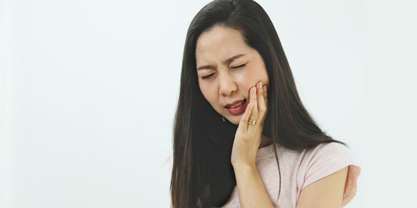 photograph of a woman holding her jaw due to TMJ pain and headache
