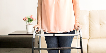 photograph of a women using a walker attained through the ontario assistive devices program