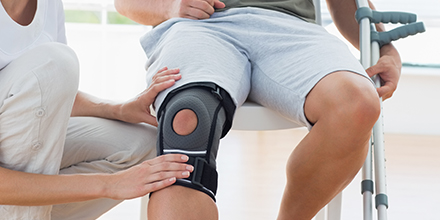photograph of a person being fitting with a custom knee brace