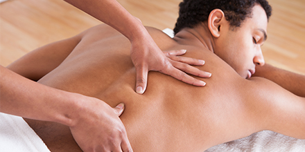 photograph of a massage therapist performing deep tissue massage therapy