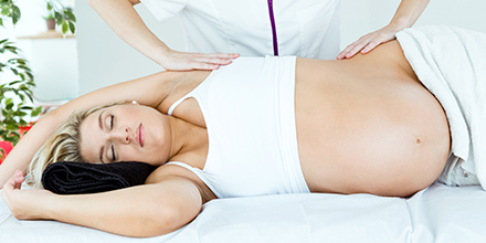 photograph of a pregnant woman getting massage therapy for low back pain while pregnant