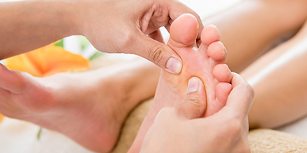 photograph of a reflexologist performing reflexology on a patient's foot