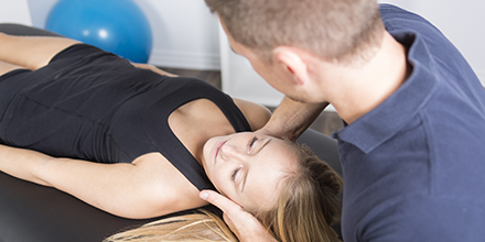 photograph of a chiropractor performing traction to reduce neck pain